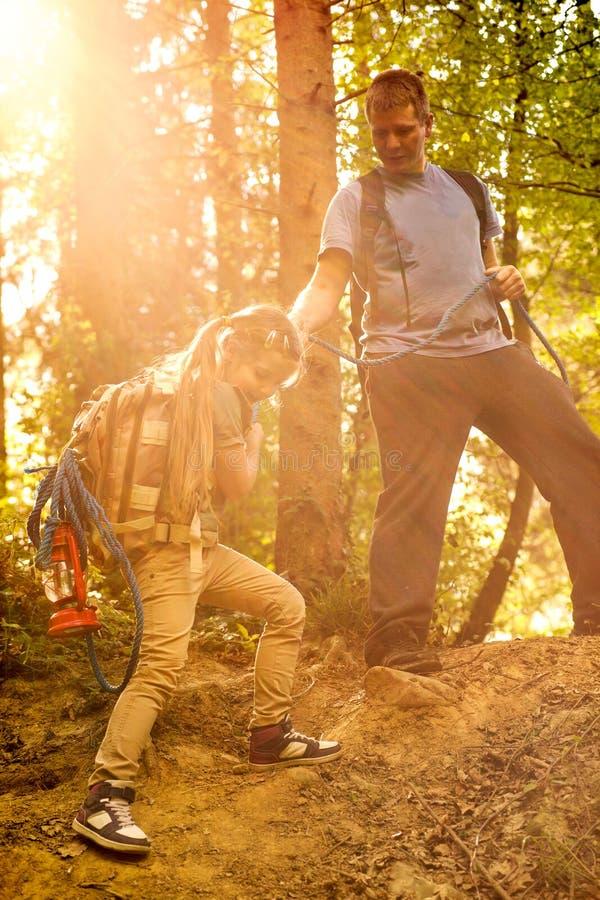 El papá ayuda a la hija a conseguir de las cuestas con la cuerda en el bosque imágenes de archivo libres de regalías