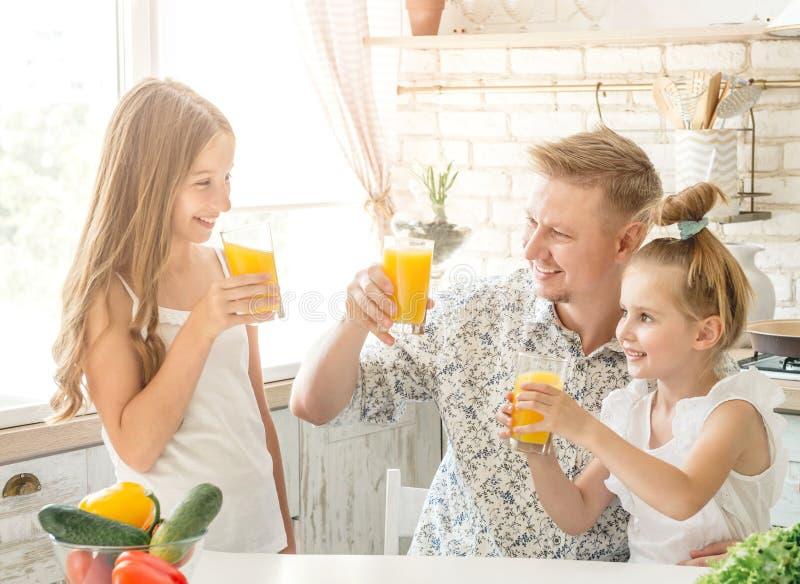 El papá con dos hijas bebe el jugo fotografía de archivo