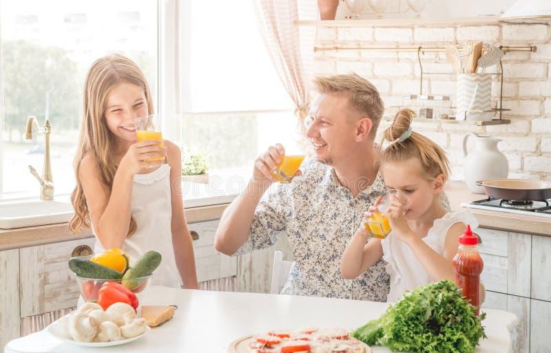 El papá con dos hijas bebe el jugo foto de archivo