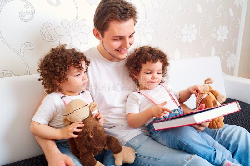 El papá con dos hijas hermana la lectura de un libro en el sofá en fotografía de archivo