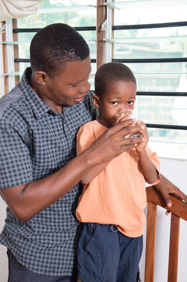 El papá da el agua a la bebida a su niño imagenes de archivo