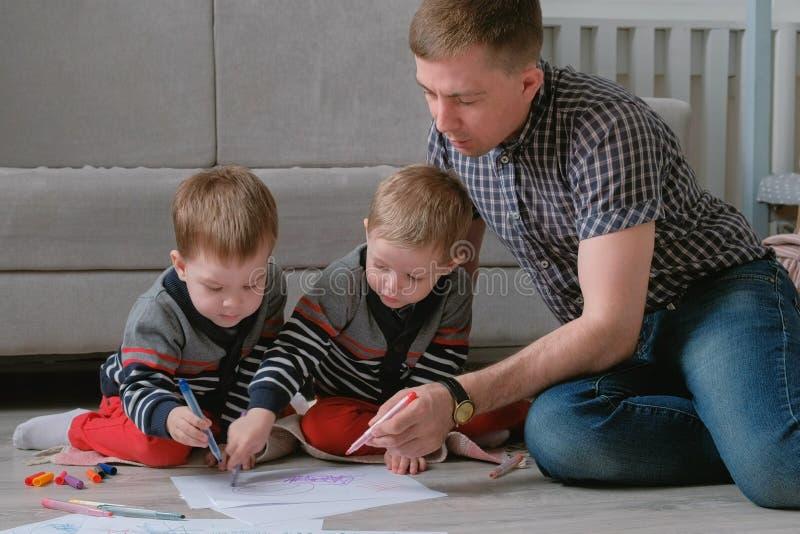 El papá de la familia y dos hermanos gemelos dibujan juntos a los marcadores y sentían plumas el sentarse en el piso fotos de archivo libres de regalías