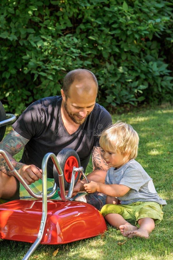 El papá enseña al hijo a utilizar el trinquete fotos de archivo