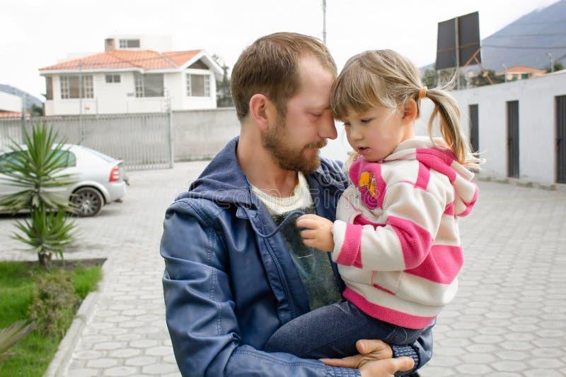 El papá está deteniendo a una hija en sus brazos fotos de archivo