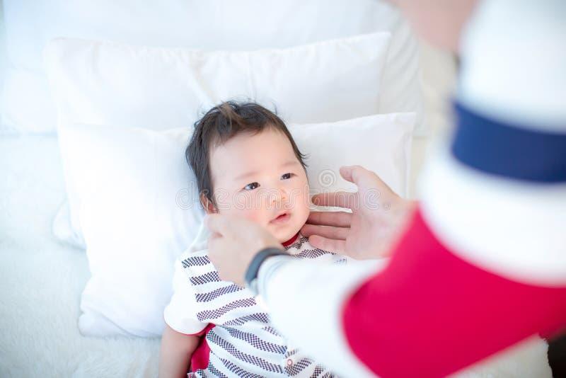 El papá está sosteniendo su mejilla del ` s del hijo con el afecto bebé y papá preciosos Relación de familia padres en educar a u imagenes de archivo