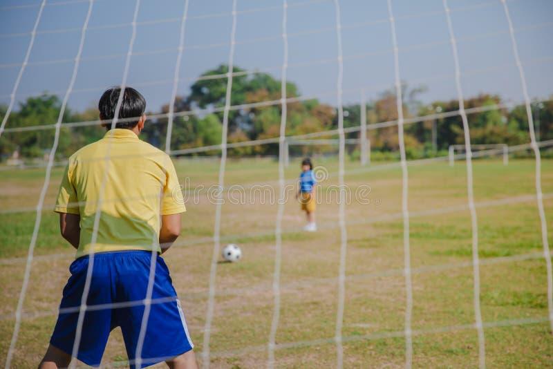 El papá hermoso con su pequeño se está divirtiendo y está jugando a fútbol foto de archivo