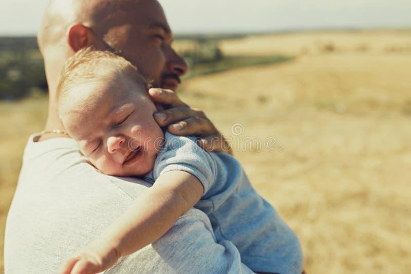 El papá joven detiene a un bebé recién nacido en su hombro, caminando en naturaleza el padre feliz está llevando pantalones corto fotografía de archivo libre de regalías