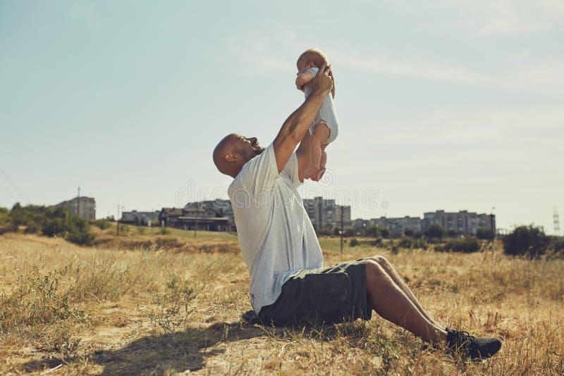 El papá joven detiene a un bebé recién nacido en sus brazos extendidos el padre feliz está llevando pantalones cortos y una camis fotografía de archivo