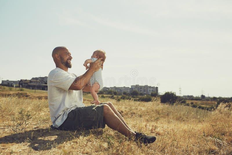 El papá joven detiene a un bebé recién nacido en sus brazos extendidos el padre feliz está llevando pantalones cortos y una camis imagen de archivo