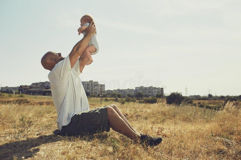El papá joven detiene a un bebé recién nacido en sus brazos extendidos el padre feliz está llevando pantalones cortos y una camis imágenes de archivo libres de regalías