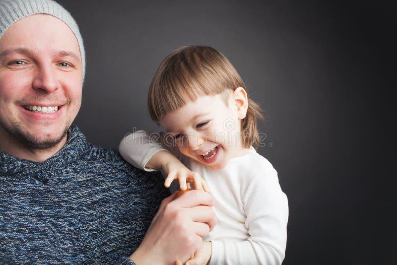 El papá juega con un pequeño hijo precioso, sentándose en sus manos en un fondo negro en el estudio Lo divierte con Apple y ellos imágenes de archivo libres de regalías