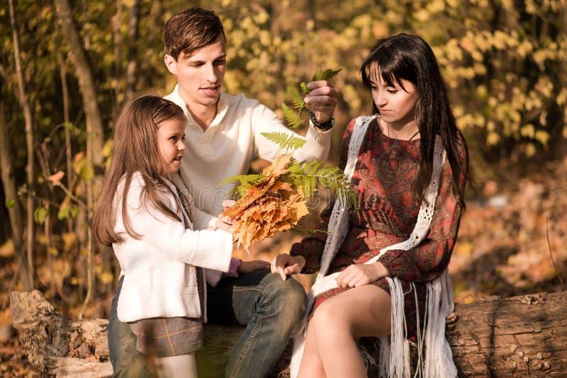 El papá, la hija y la mamá pasan el tiempo junto en el bosque del otoño foto de archivo libre de regalías