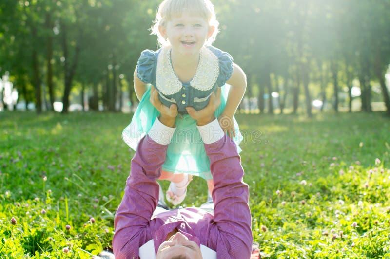 El papá mantiene a la hija sus brazos imagen de archivo