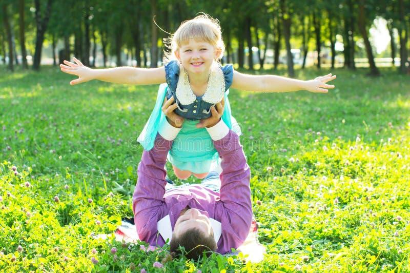 El papá mantiene a la hija sus brazos en naturaleza imagen de archivo