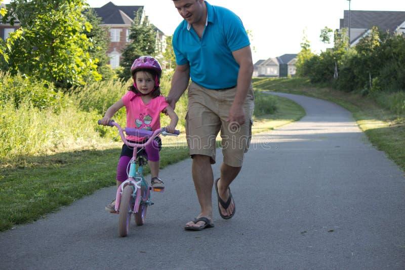El papá que ayuda a su hija monta su bicicleta fotografía de archivo