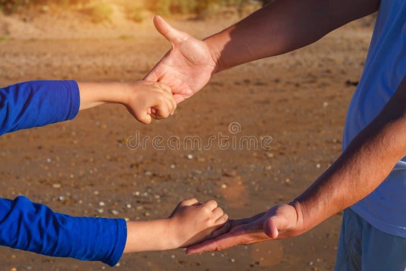 El papá sostiene de común acuerdo el primer de la mano del ` s del hijo fotos de archivo