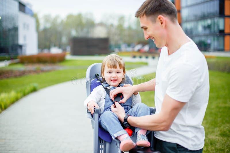 El papá sujeta sus cinturones de seguridad del ` s de la hija antes de montar una bici foto de archivo libre de regalías