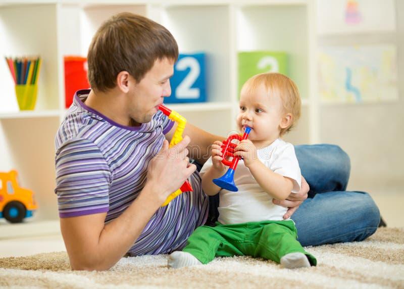 El papá y el hijo felices de la familia juegan los juguetes musicales fotografía de archivo