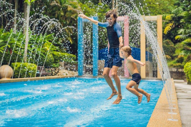 El papá y el hijo se divierten en la piscina foto de archivo