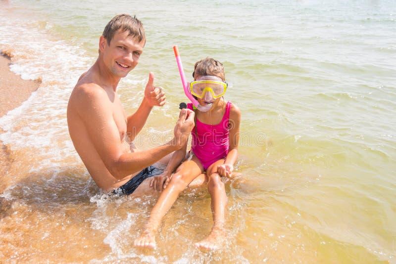 El papá y la hija están considerando la cáscara subacuática encontrada imagenes de archivo