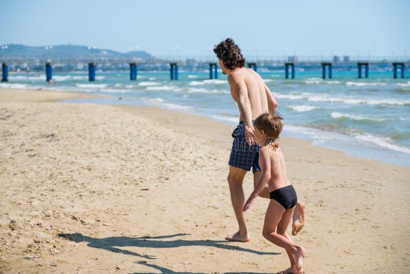 El papá y su hijo corren a lo largo de la playa al embarcadero en troncos de natación Día de fiesta de la playa foto de archivo