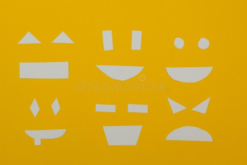 El papel cortado hace frente en un fondo amarillo ilustración del vector