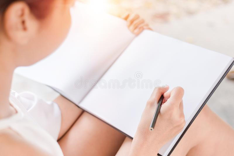 El papel de escribir hermoso de las mujeres en la tierra en el parque imagenes de archivo