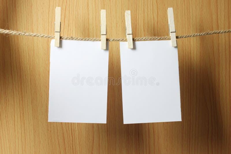 El papel en blanco cuelga en la cuerda marrón con los clips de papel de madera en w fotos de archivo