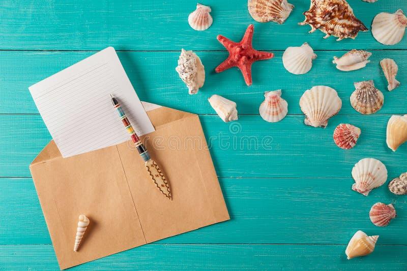 El papel para las notas acerca a conchas marinas en fondo de madera foto de archivo libre de regalías
