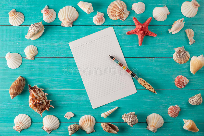 El papel para las notas acerca a conchas marinas en fondo de madera Copie el espacio foto de archivo libre de regalías