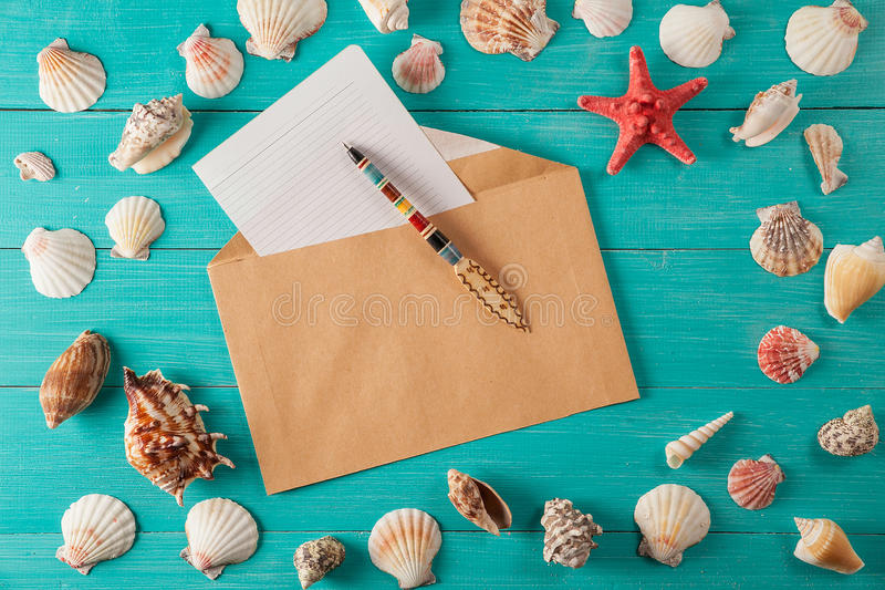 El papel para las notas acerca a conchas marinas en fondo de madera Copie el espacio imagenes de archivo