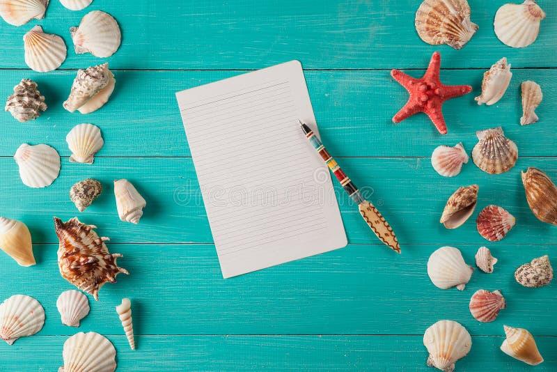 El papel para las notas acerca a conchas marinas en fondo de madera Copie el espacio imágenes de archivo libres de regalías
