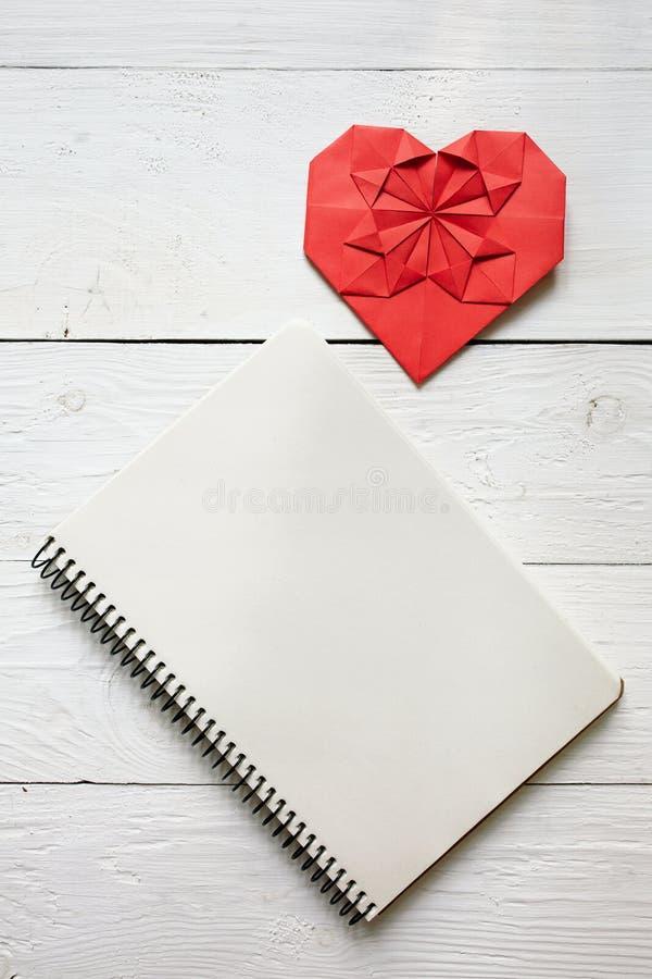 El papel rojo dobló el corazón en la tabla rústica de madera pintada blanca, visión superior de la papiroflexia Decoración del sí fotos de archivo