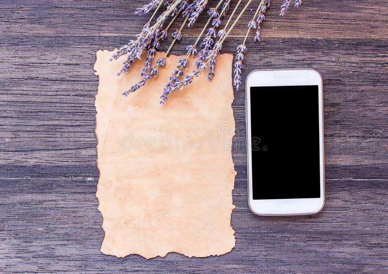 El papel viejo y el teléfono elegante con lavanda florecen en TA de madera oscura fotos de archivo