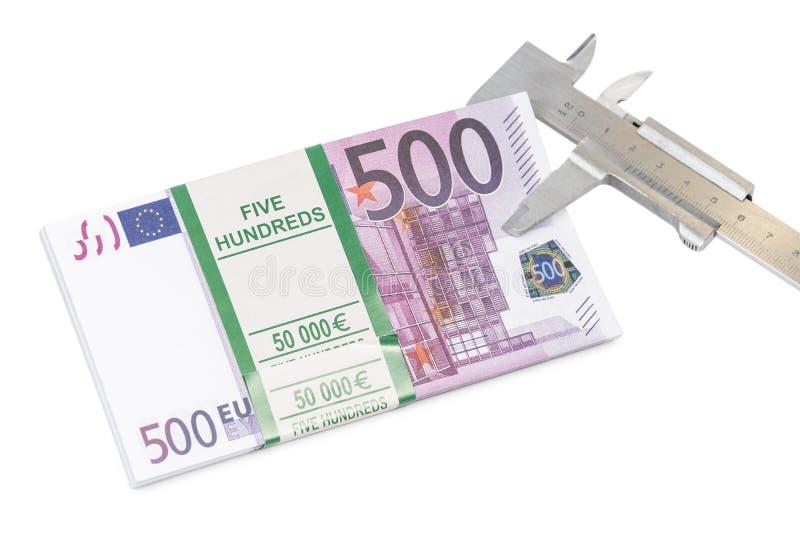 El paquete de dinero es medido por el calibrador imágenes de archivo libres de regalías