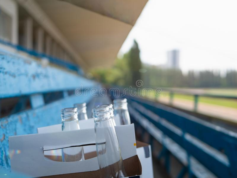 El paquete del primer de botellas de cerveza vacías se fue por la gente en estadio vacío después de partido de deporte Foco selec imagenes de archivo
