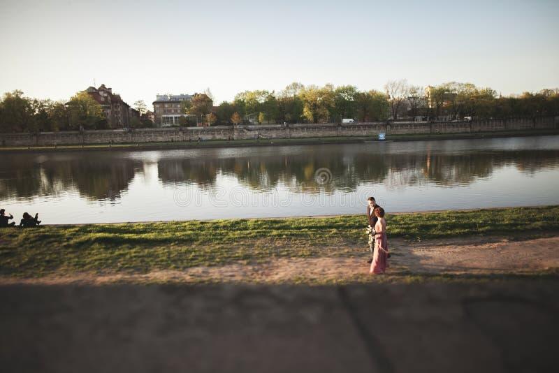 El par único hermoso camina en su día de boda en Kraków cerca del río Visla fotos de archivo