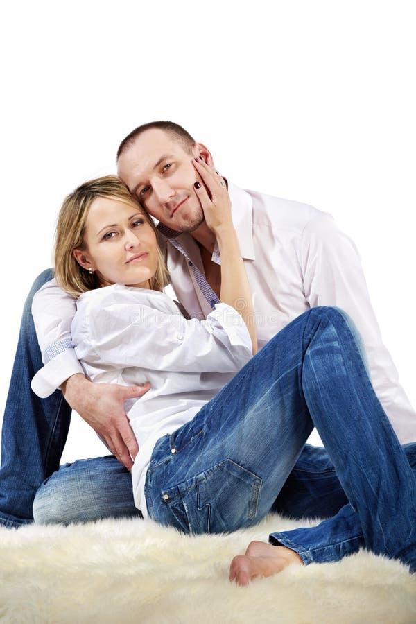El par abrazado se sienta en la alfombra blanca imagen de archivo