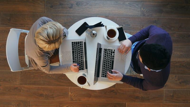 El par acertado joven del negocio está discutiendo los documentos, café de consumición y está sonriendo mientras que trabaja en c imágenes de archivo libres de regalías