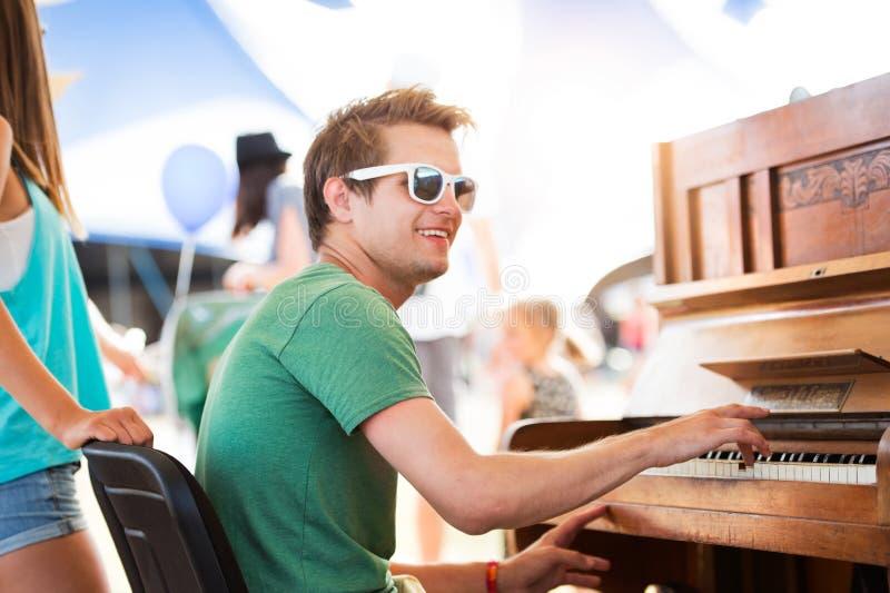 El par adolescente en el festival de música del verano, muchacho juega el piano fotografía de archivo libre de regalías