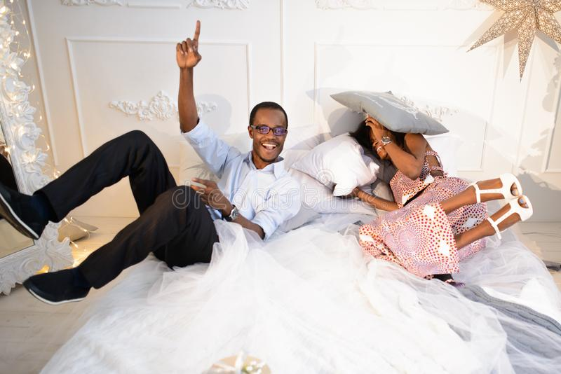 El par afroamericano cariñoso feliz está consiguiendo loco en la Nochebuena cerca del árbol del Año Nuevo, él está mintiendo ence imágenes de archivo libres de regalías
