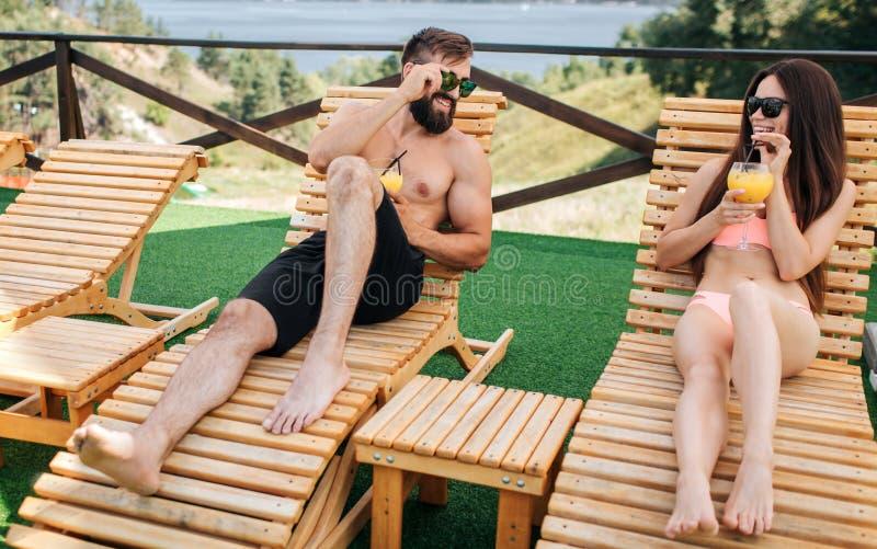 El par agradable y positivo está mintiendo en sunbeds y cócteles del control en manos Miran uno a y llevan las gafas de sol fotografía de archivo libre de regalías