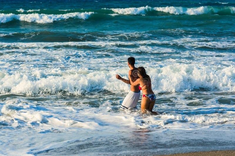 El par alegre feliz que se divierte que corre y que juega al mar junto y que hace salpica del agua imagen de archivo