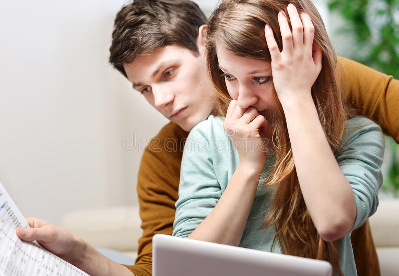 El par ansioso joven consulta su cuenta bancaria foto de archivo libre de regalías