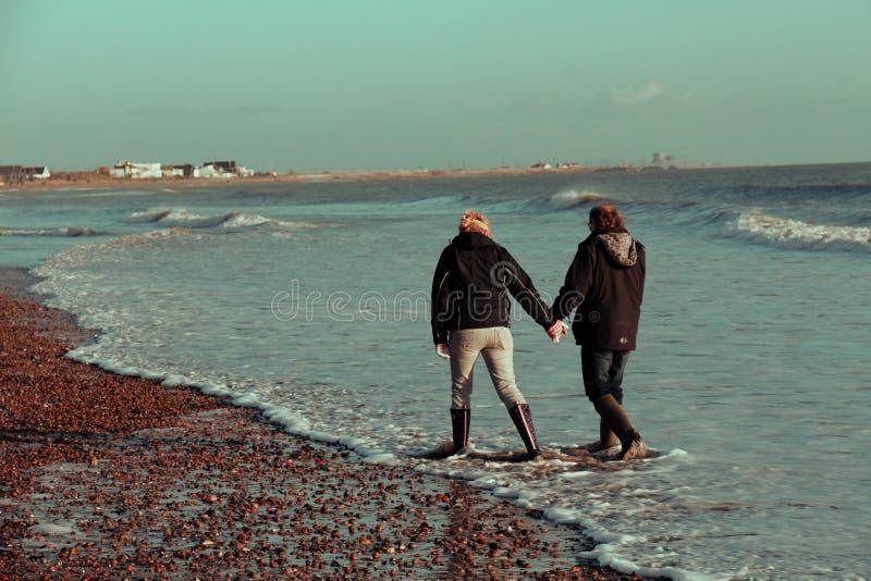 El par camina a lo largo de una playa BRITÁNICA en el invierno fotos de archivo