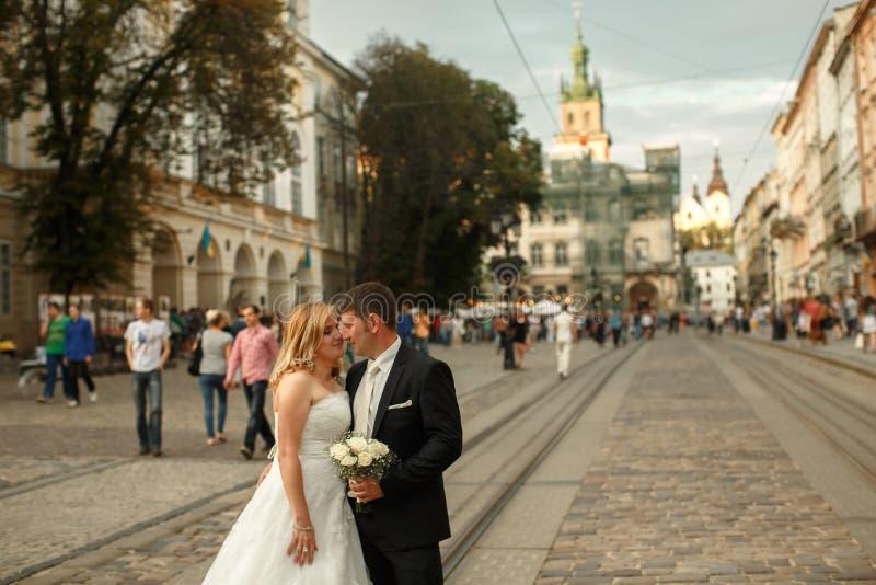 El par cansado de la boda abraza la situación en la calle vieja fotos de archivo libres de regalías
