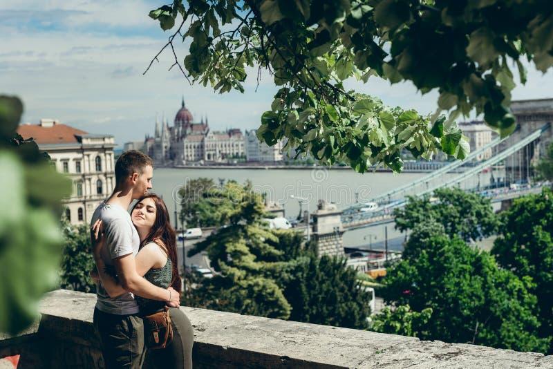 El par cariñoso bastante joven está abrazando suavemente en el balcón mientras que disfruta del panorama hermoso de Budapest, Hun fotografía de archivo libre de regalías