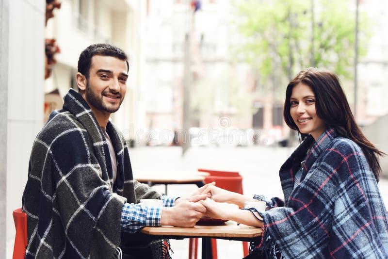 El par cariñoso en mantas se sienta en la tabla imagen de archivo libre de regalías
