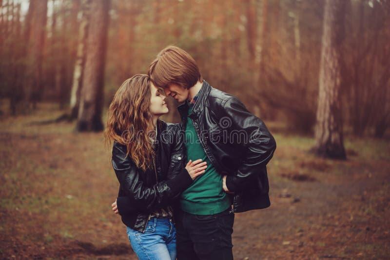 El par cariñoso feliz joven en las chaquetas de cuero abraza al aire libre en paseo acogedor en bosque imagen de archivo