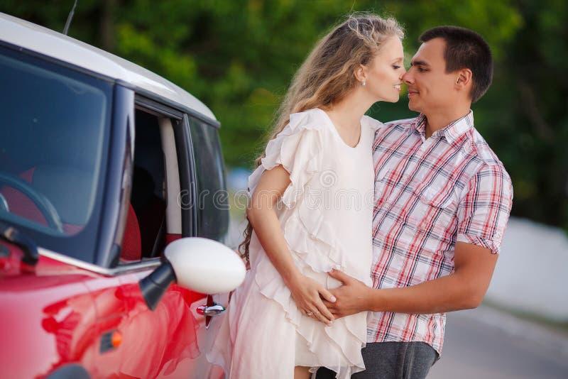 El par cariñoso feliz viaja en el coche rojo foto de archivo
